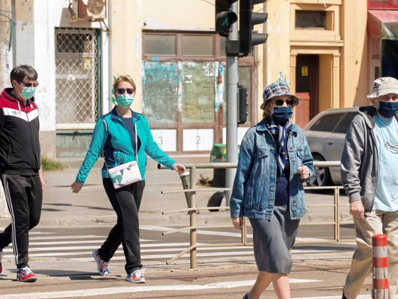 Foto von mehreren Menschen mit Maske auf einer Straße